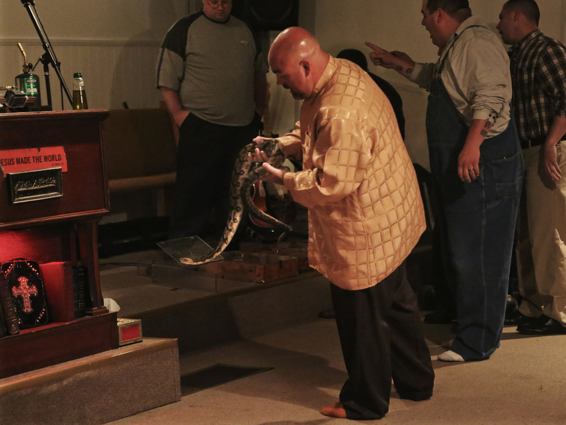 Pastor Jamie Coots holds a snake at Full Gospel Tabernacle in Jesus Name Church of Middlesboro, Ky. [Source: NPR]